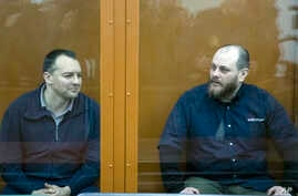 The former chief of the cybercrime department at Russia's main domestic security agency Sergei Mikhailov, left, and the former employee of Kaspersky Lab cybersecurity firm Ruslan Stoyanov attend a hearing in a court in Moscow, Russia, Feb. 26, 2019.