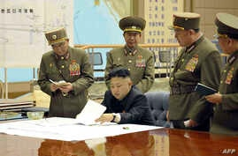 This photo taken and released by North Korea's official Korean Central News Agency (KCNA) on March 29, 2013 shows, according to KCNA, North Korean leader Kim Jong-Un discussing the strike plan with North Korean officers during an urgent operation mee