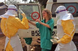 In this photo provide by MSF, healthcare workers prepare isolation and treatment areas for Ebola in Gueckedou, Guinea, Mar. 28, 2014.