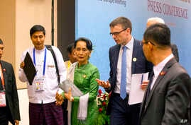 FILE - Aung San Suu Kyi talks with  Estonia Foreign Minister and a representative of EU Sven Mikser, second right, as they leave a press conference after the Asia Europe Foreign Ministers (ASEM) at Myanmar International Convention Centre (MICC), Nov.