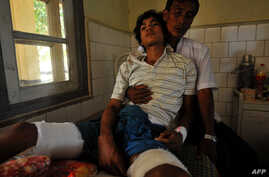 An injured Rakhine Buddhist man leans on his father at a hospital in Sittwe, the capital of Myanmar's western Rakhine state after they were recently injured at the four different districts outside Sittwe, October 26, 2012.