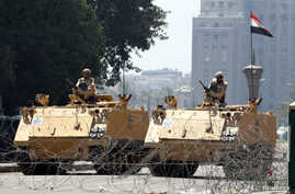 Egyptian soldiers stand guard as they close one of the entrances to Tahrir Square in Cairo, Aug. 23, 2013.