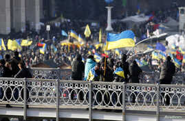 A man carrying an Ukranian flag gestures as he stands on top of a bridge overlooking Independence Square in Kiev December 4, 2013. Ukraine's prime minister warned protesters blockading government buildings on Wednesday that anybody guilty of violatin