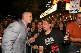 """John Cena greets fans as he arrives for the world premiere of """"Blockers"""" during the South by Southwest Film Festival at the Paramount Theatre on March 10, 2018, in Austin, Texas."""