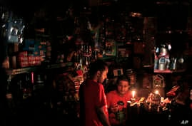 A Bangladeshi salesman interacts with a customer during a blackout in Dhaka, Bangladesh, Nov. 1, 2014.
