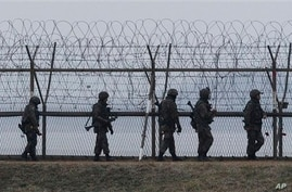 South Korean army soldiers patrol along a barbed-wire fence near the border village of the Panmunjom, in Paju, South Korea, Monday, April 8, 2013. North Korea said Monday it will recall 51,000 North Korean workers and suspend operations at a factory