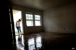 FILE - In this Aug. 31, 2017 file photo, Alejandra Castillo takes a break from carrying water-soaked items out of her family's home after flood waters receded in Houston. Experts say Harvey's filthy floodwaters pose significant dangers to human saf...