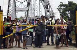 FILE - People stand next to a closed gate as they wait to try to cross La Union international bridge, on the border with Colombia at Boca de Grita in Tachira state, Venezuela, Aug. 29, 2015.