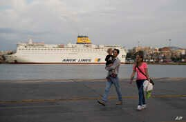 A couple with their child walk in front of a docked ferry at the port of Piraeus near Athens, May 16, 2017.