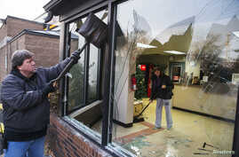 Business owner Jim Bolin and Mary Sue Patterson work to clean up their vandalized car care center following a second night of protests in Ferguson, Missouri, Nov. 26, 2014.
