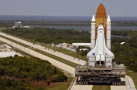 Space Shuttle Discovery, resting on the Mobile Launcher Platform, turns the corner on the crawlerway as it rolls back from Launch Pad 39B to the Vehicle Assembly Building, March 26, 2005. (Image Credit: NASA/KSC)