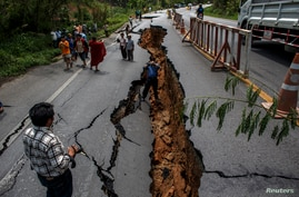 People walk on a highway road damaged by Monday's earthquake in Chiang Rai, in northern Thailand, May 6, 2014.