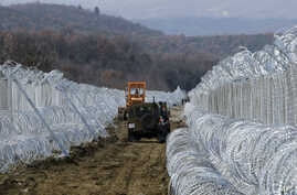 Macedonian Army vehicles move along a path between two lines of fence reinforced with razor wire, on the border line with Greece near the southern Macedonia's town of Gevgelija, Sunday, Feb. 14, 2016.