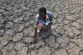 FILE - Last Zimaniwa feels the broken ground at a spot which is usually a reliable water source that has dried up due to lack of rains in the village of Chivi , Zimbabwe, Jan. 29, 2016. Southern Africa's lengthy drought has gotten worse, aid official