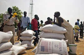 Southern Sudanese who recently returned from northern Sudan receive food rations from the World Food Program in the southern capital of Juba on Friday, Jan. 7, 2010.