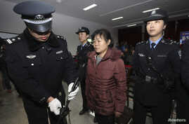 Zhang Shuxia, an obstetrician involved in baby trafficking, stands trial in Weinan Intermediate People's Court in Weinan, Shaanxi province, Dec. 30, 2013.