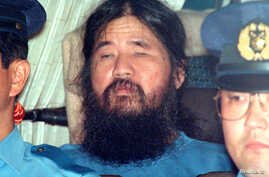 Japanese doomsday cult leader Shoko Asahara sits in a police van following in Tokyo, Japan, Sept. 25, 1995.