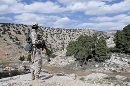 FILE - A Lebanon Hezbollah fighter carries his weapon as he stands in Khashaat, in the Qalamoun region after they advanced in the area, May 15, 2015.