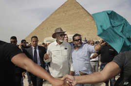 Actor Morgan Freeman, center left, is surrounded by bodyguards as he visits the Giza Pyramids, just outside Cairo, Egypt, Oct. 23, 2015.