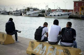 FILE - Unaccompanied minors from north Africa sit next to the river Tiber, in Fiumicino, Italy, 30 kilometers (19 miles) west of Rome, April 21, 2016.