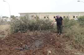 A member of the February 17th Brigade, points at the site of a bombing at the brigade's base after it was bombed by two jets in Benghazi, Libya, May 28, 2014.