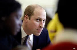 Britain's Prince William speaks with families who have lost loved ones during his visit to a child bereavement center in Stratford in east London, Jan. 11, 2017.