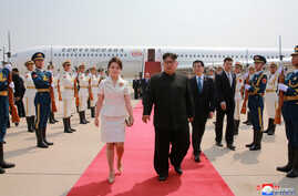 North Korean leader Kim Jong Un and his wife Ri Sol Ju walk upon arriving in Beijing, China, in this undated photo released June 20, 2018 by North Korea's Korean Central News Agency.