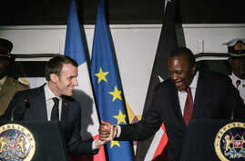 French President Emmanuel Macron, left, shakes hands with Kenyan President Uhuru Kenyatta during an event at Nairobi Central Railway Station in Nairobi, March 13, 2019, on the first day of a state visit to Kenya.