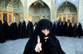 An Iranian woman displays her ink-stained finger after voting in the parliamentary and Experts Assembly elections at a polling station in Qom, Feb. 26, 2016.