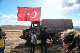 FILE - A man waves a Turkish national flag as a Turkish army vehicle drives past during a demonstration in support of the Turkish army's operation near the Turkey-Syria border near Reyhanli, Hatay, on Oct. 10, 2017.
