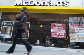 A passersby walks in front of a help wanted sign at a McDonalds restaurant in the Brooklyn borough of New York, March 7, 2014. U.S. job growth rose more than expected in February, easing fears of an abrupt slowdown in economic growth and keeping the