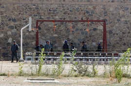 FILE - In this Oct. 8, 2014, photo, police officers take positions by nooses prepared to execute men at a jail in Kabul, Afghanistan. Afghanistan has hanged six men convicted of terrorism, signaling a tougher approach toward the Taliban.