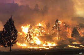 In this photo released July 6, 2018, by the California Highway Patrol, the Klamathon Fire burns in Hornbrook, California.