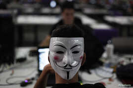 "A man wearing a Guy Fawkes mask surfs the web during a ""Campus Party"" Internet users gathering in Sao Paulo, January 30, 2013."