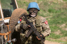 FILE - A United Nations peacekeeping soldier provides security during a food aid delivery by the United Nations Office for the Coordination of Humanitarian Affairs and world food program in the village of Makunzi Wali, Central African Republic, April