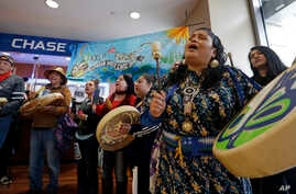 FILE - Roxanne White, right, a member of the Yakama Nation, sings during a protest inside a Chase bank branch, May 8, 2017, in Seattle. Climate activists opposed to oil pipeline projects have called on several financial institutions not to help build