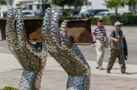 """Pedestrians walk by artist Heath Satow's sculpture """"Reflect,"""" made with a damaged, rusted I-beam from the collapsed World Trade Center buildings, outside the Rosemead, California, city hall plaza. Aug. 26, 2016."""