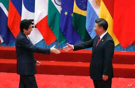 FILE - Japanese Prime Minister Shinzo Abe, left, and Chinese President Xi Jinping approach each other for a handshake before a group photo session for the G-20 Summit in Hangzhou, in eastern China's Zhejiang province, Sept. 4, 2016. The two will meet