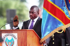 FILE - Incumbent Congo President Joseph Kabila holds the Congolese flag as he takes the oath of office as he is sworn in for another term, in Kinshasa, Democratic Republic of Congo.