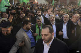 The exiled Hamas chief, Khaled Meshaal (L), and Gaza's Hamas prime minister, Ismail Haniyeh, wave as they parade through the streets following Meshaal's arrival in Gaza City December 7, 2012.