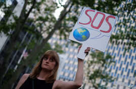 A woman displays a placard during a demonstration in New York on June 1, 2017, to protest US President Donald Trump's decision to pull out of the 195-nation Paris climate accord deal.
