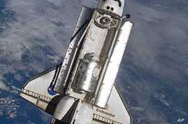 Space shuttle Endeavour with the Tranquility node and cupola inside its payload bay is seen from the International Space Station prior to docking.