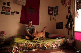 Yassin Mohammed sits with a cat in an apartment he shares, in Cairo, Egypt, Oct. 4, 2018. Mohammed, who walked free last month after serving a two-year sentence for joining a protest, secretly chronicled life in his cell block with his artwork, givin