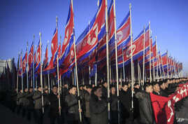 North Koreans parade with the North Korean flag in Kim Il Sung Square in Pyongyang, North Korea, Thursday, Feb. 25, 2016, to show their loyalty to the Workers' Party.