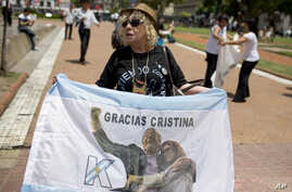 """A government supporter holds an Argentine flag that reads in Spanish """"Thanks Cristina"""" featuring an image of late President Nestor Kirchner and his wife, current President Cristina Fernandez in Buenos Aires, Argentina, on Dec. 9, 2015."""