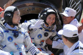 Liu Yang, center, China's first female astronaut, waves next to her comrade Jing Haipeng, left, as she exits re-entry capsule of China's Shenzhou 9, Siziwang Banner, Mongolia, June 29, 2012 file photo.
