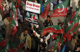 A supporter of Pakistan's Tehreek-e-Insaf party, headed by cricketer-turned politician Imran Khan, holds up a poster and shouts slogans during a protest against U.S. drone strikes in Pakistan, in Peshawar, Pakistan, Nov. 23, 2013.