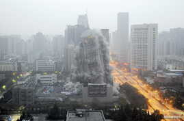 FILE 0 A building crumbles during a controlled demolition to make way for a new commercial center in Xi'an, Shaanxi province, China.