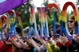 "Members of Capital City Pride and others from the LGBT community hold up letters spelling out ""Orlando"" to honor of the recent shooting at a gay nightclub days earlier before the raising of a rainbow flag in front of the Washington state Capitol, Jun..."