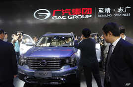 Journalists stand by as Chinese officials examine the Chinese automaker GAC's GS8 SUV after it was unveiled at the Beijing International Auto Show in Beijing, April 25, 2016.